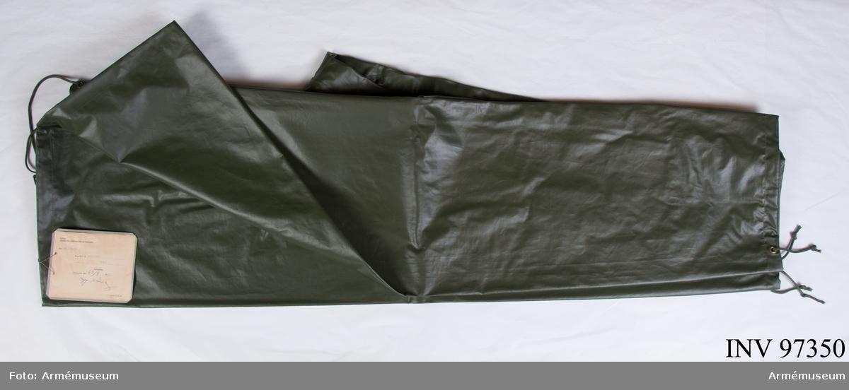 """Byxor av grön plastad väv. Vihängande etikett: """"Kungl. Arméintendenturförvaltningen, Dnr MB 2375/60, Modell å Regnställ: byxor, fastställes Stockholm den 23/9 1960, H. Kring, Kaserntr KA 59 638"""". På baksidan: """"M 7379-106000""""."""