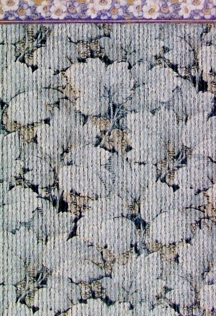 Ett tätt ytfyllande delvis sgrafferat blommönster i flera ljusblå nyanser. Textilimiterande.      Tillägg historik: Tapet upphittad på vinden i föräldrarhem från ca 1890.