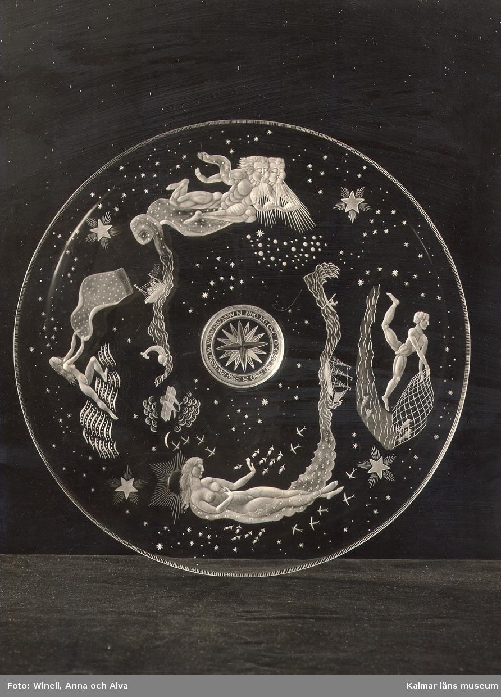 Ett graverat glasfat. Motiv av en fiskare, två män som blåser, två kvinnor och vatten med några skepp.