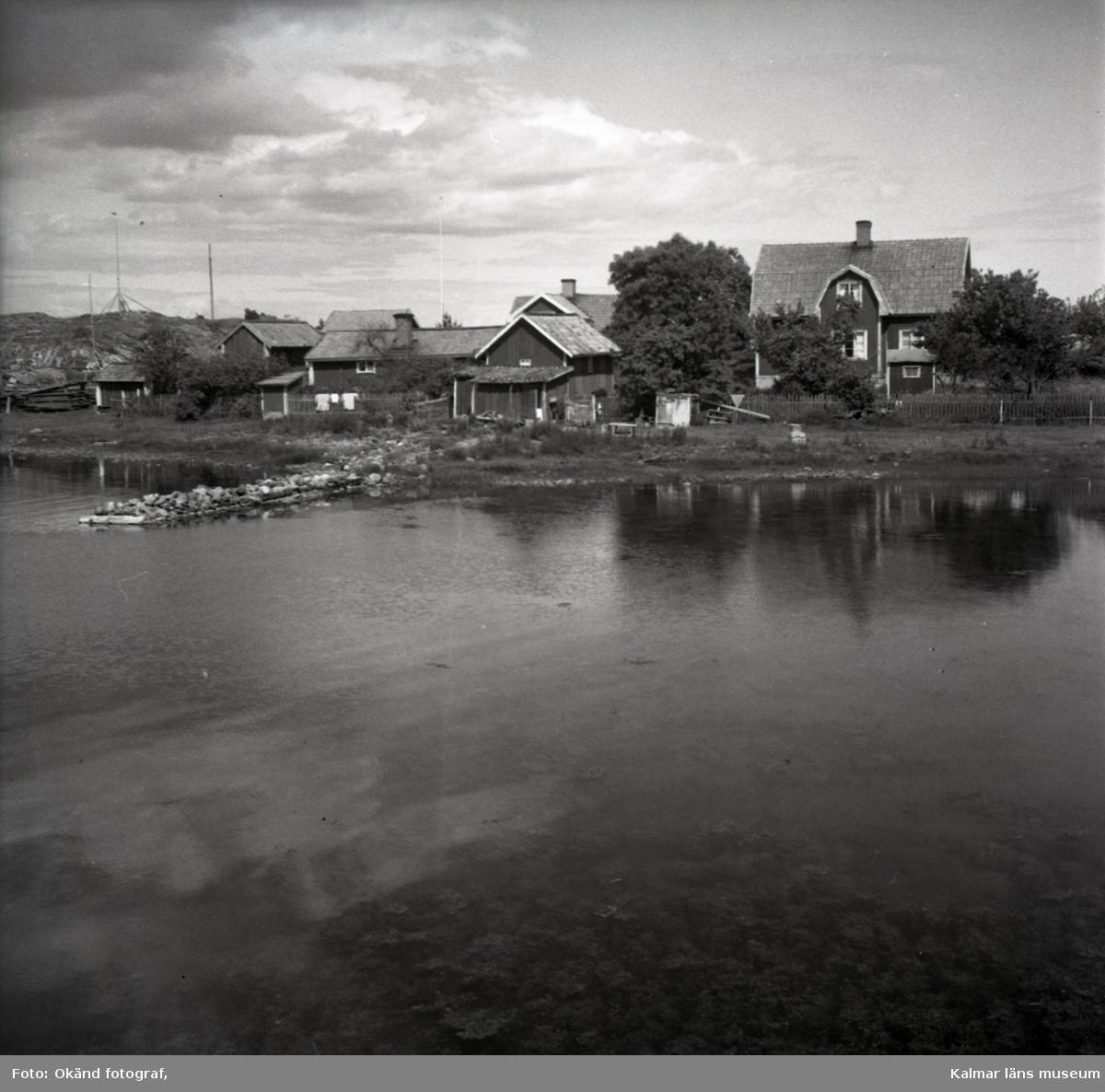 Ett fiskeläge med sjöbodar och bostadshus.
