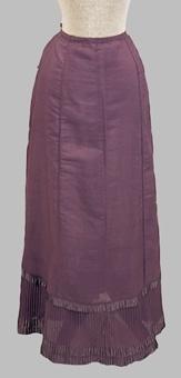 Rödaktigt blå (violett) kjol sydd av tuskaftsväd halvyllekvalité. Modellen består av fem kilformade våder av olika storlek. Nedtill är kjolen avslutad med en plisserad kant. Dragsko längs midjan baktill. Sprund mitt bak. Sidenband pryder underkjolen nedtill. Underkjolen är maskinsydd.   Neg.nr:  Sakord: UNDERKJOL Tillverkningstid: 1890-1920 Material: Ull bomull silke Teknik: Vävt sytt plisserat Mått: L=990 Vikt: