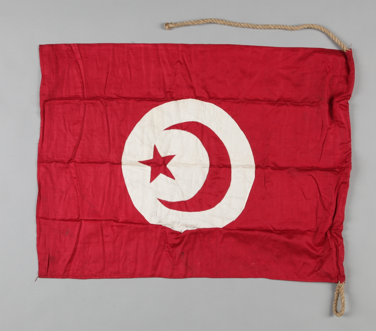 Rødt flagg med rund sirkel med halvmåne og stjerne i hvitt.