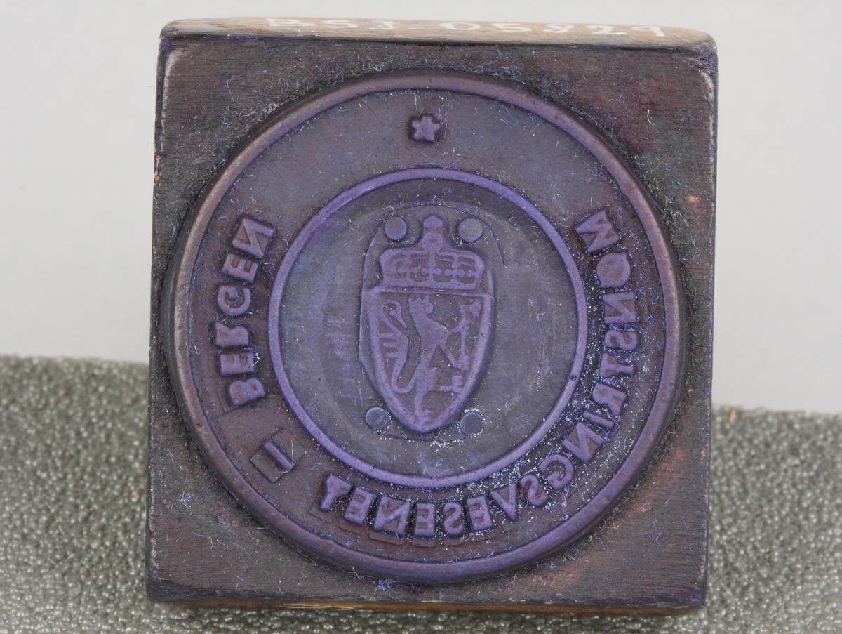 Stempel i tre med tekst ytterst og våpenskjold med den norske løve i midten.