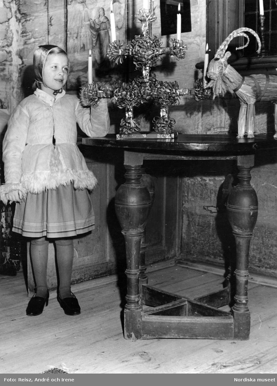 Flicka vid bord med julljusstake och halmbock