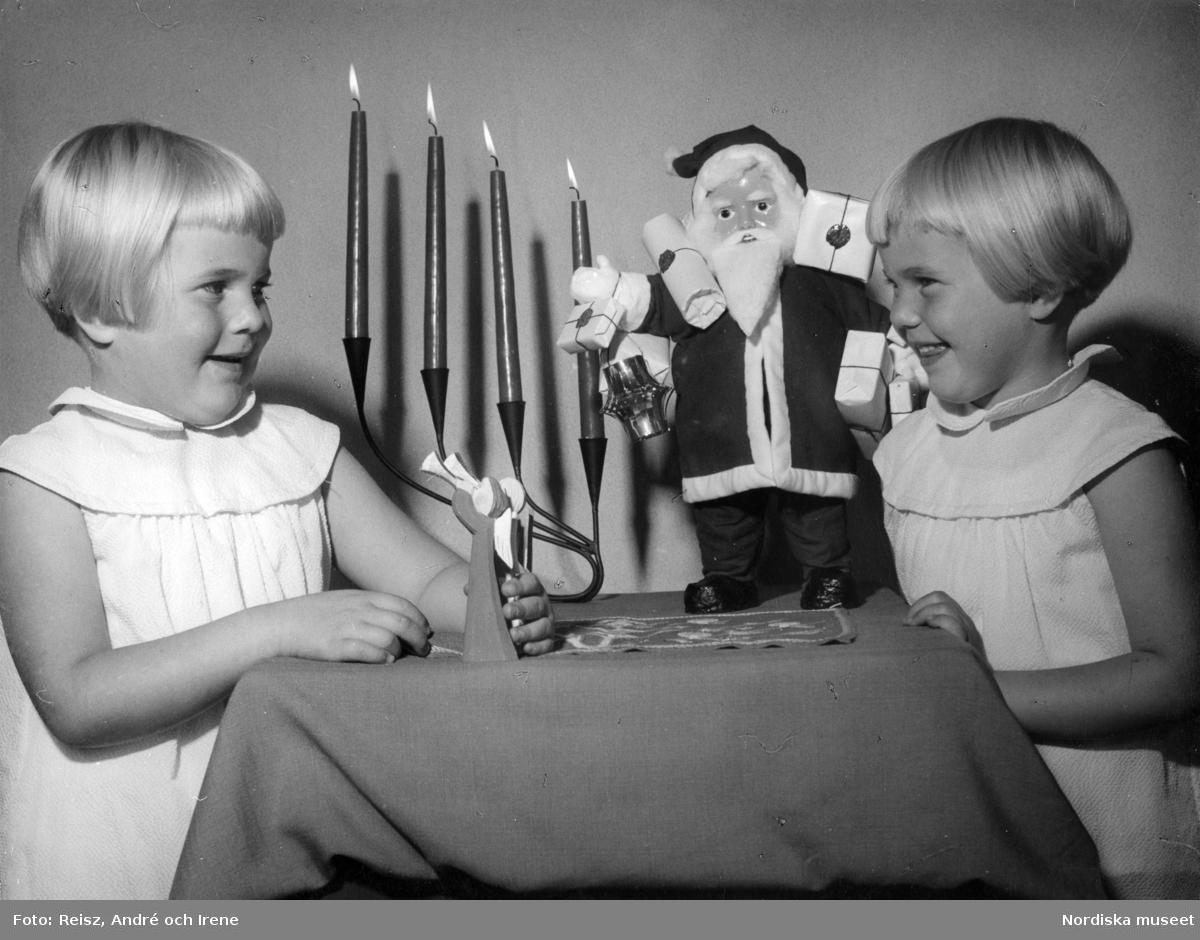 Två flickor i ljusa klänningar vid bord med adventsljusstake och tomtefigur