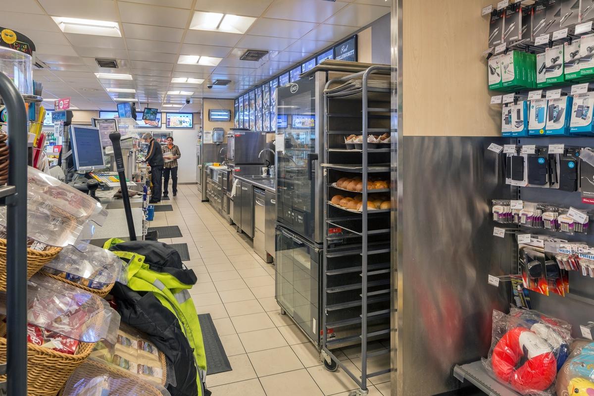 Statoil Dal. Butikk interiør bak butikkdisk. Bakervarer og kjøkkenbenk . Butikkbetjeningens jobb-ytterklær ligger fremme til bruk.