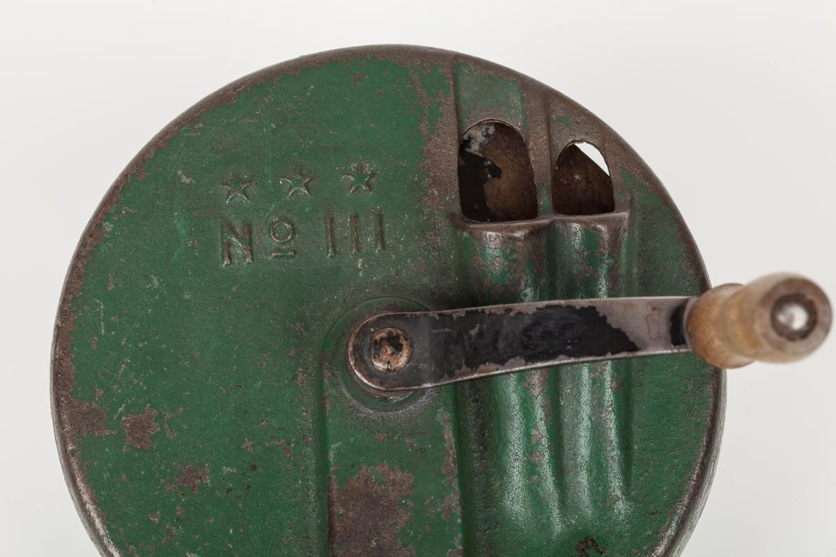 snittemaskinen består av tre deler: a) hoveddelen med i hel metall, grønnmalt, har 2 ilegg. b) snitteflaten med tre skarpe kniver. Alle montert med to skiver hver. Knivene er blanke og laget av rustfritt stål. Montasjeplaten er sortmalt metall. c) Sveiv av metall med håndtak av tre. metallet er sortmalt. Håndtaket er ubehandlet.