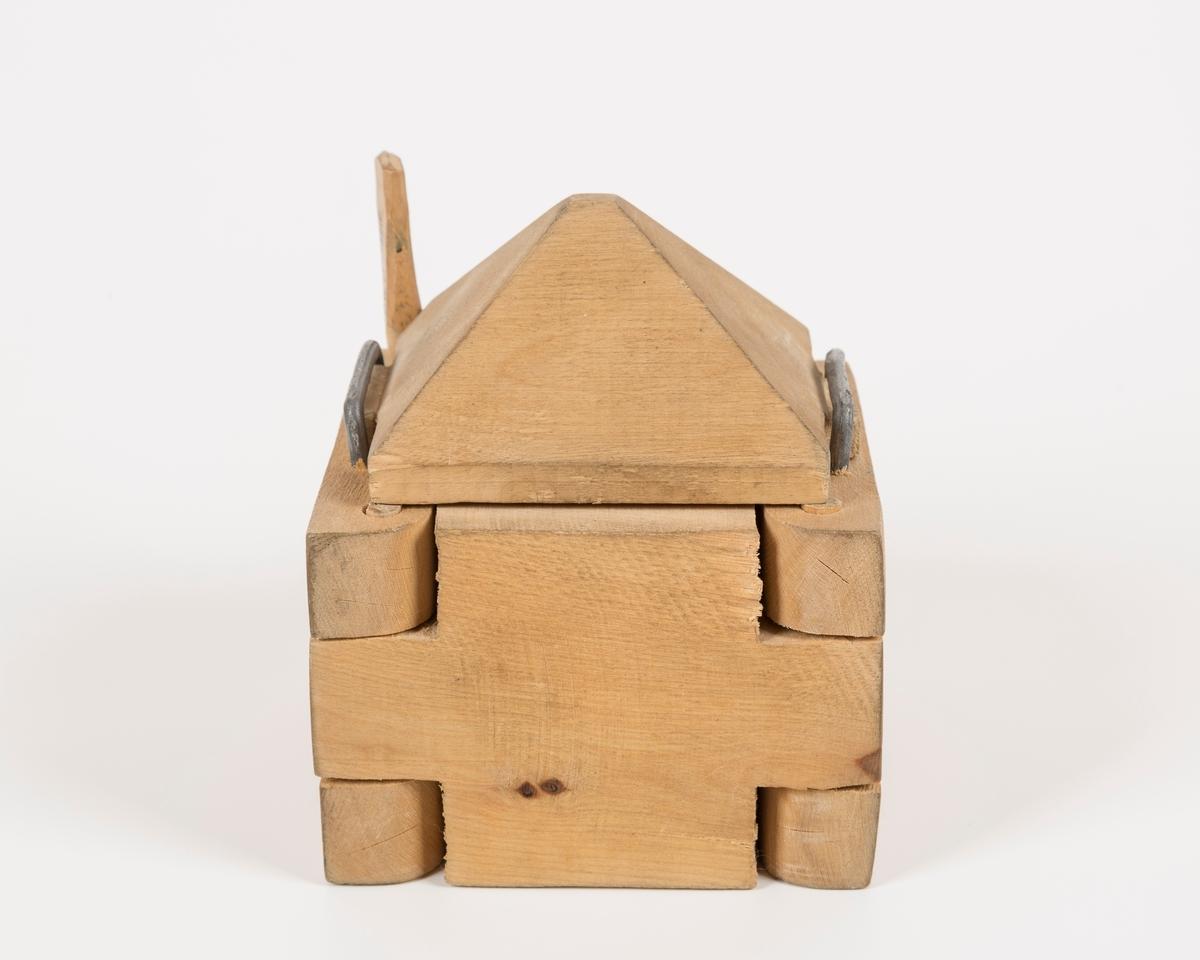 Kvadratisk form med pyramidelokk. Dekor har 5 ulike mønstre. Alle hjørner er bevegelige - trenagler - en kan tas ut. Lokket festes ved hjelp av 2 små hanker i to metallhemper. Innvendig er det mønster - blomst og buer med blad. toppen er hellelagt som et tak. Formen har ingen bunn. Formen består av tre deler: a) form b) lokk c) nagle