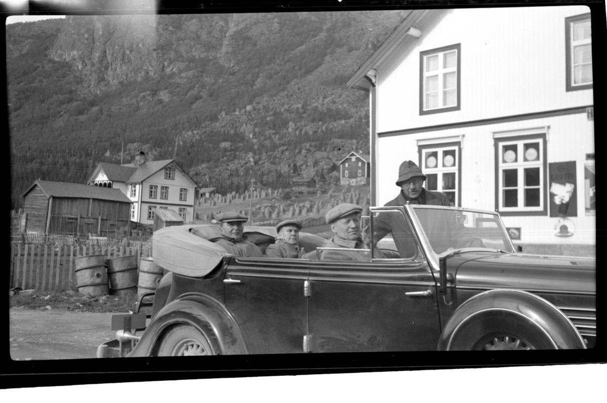 Johan Buratti, Erling Lorck sitter bak i bilen (Buick 1934-35 convertible sedan) mens Harsem sitter i forsetet sammen med stående Rolf Sundt sr., Vannevik, Hemsedal. To gårder ligger i bakgrunnen . Fotografert 1938.