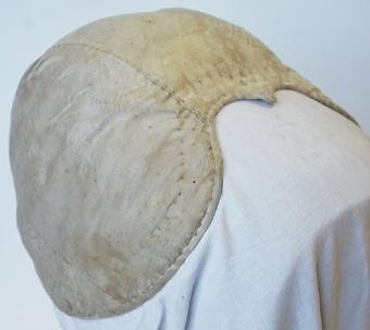 Bindmössa klädd med beige sidentyg och med tuskaftvävt foder av linne.