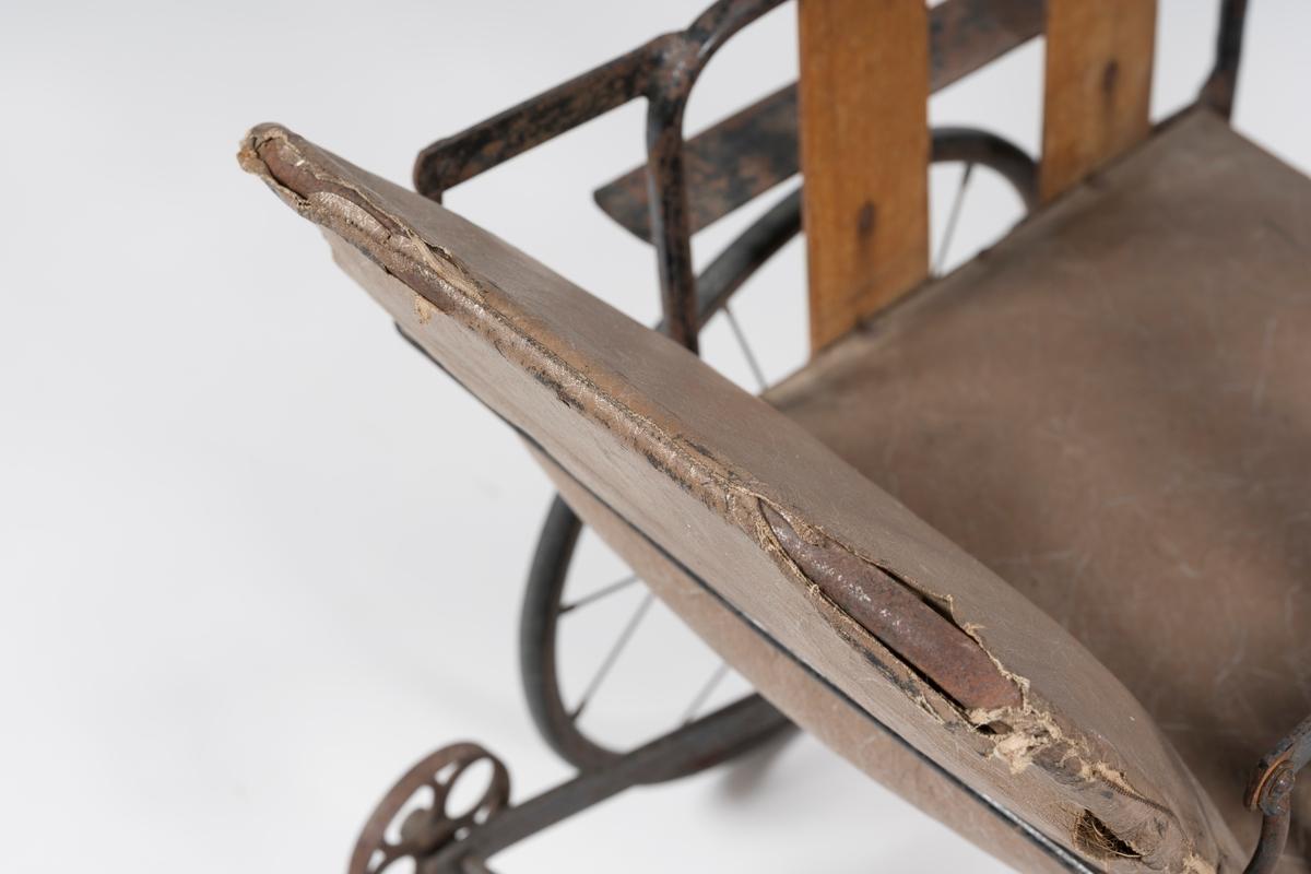 Understell og hjul av jern. Setet m/stopp og lerretsovertrekk. Rygg jernramme m/stopp og lerretsovertr. Lærstropp festet i messingknott