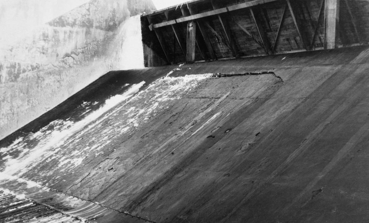 """Detalj fra tømmerløpet i kraftverksdammen som ble bygd ved Osfallet i elva Søndre Osa i Åmot kommune i Hedmark.  Fotografiet er tatt i september 1915, et snaut år etter at kraftverket ble satt i drift.  På opptakstidspunktet var det åpenbart liten vanngjennomstrømming i elva, slik at en lett kunne se den glatte betongen som bare delvis var dekt av et tynt vannslør.  Osdammen ble ødelagt under vårflommen i 1916, og dambruddet forårsaket store skader på det nye anlegget, noe som innebar betydelige økonomiske tap for utbyggerne, Åmot kommune.  Mer informasjon om kraftutbygginga ved Osfallet og det påfølgende dambruddet finnes under fanen """"Opplysninger""""."""