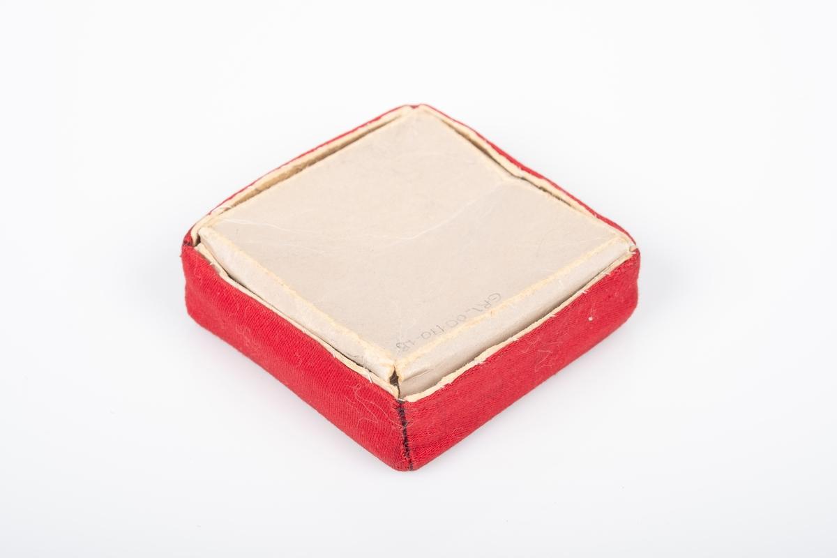 Eske med bunn og lokk med bomull i. Esken er av papp. Lokket er trukket over med tekstil (bomull) i rødt og rutete mønster. Bunnens kanter kan brettes ut.