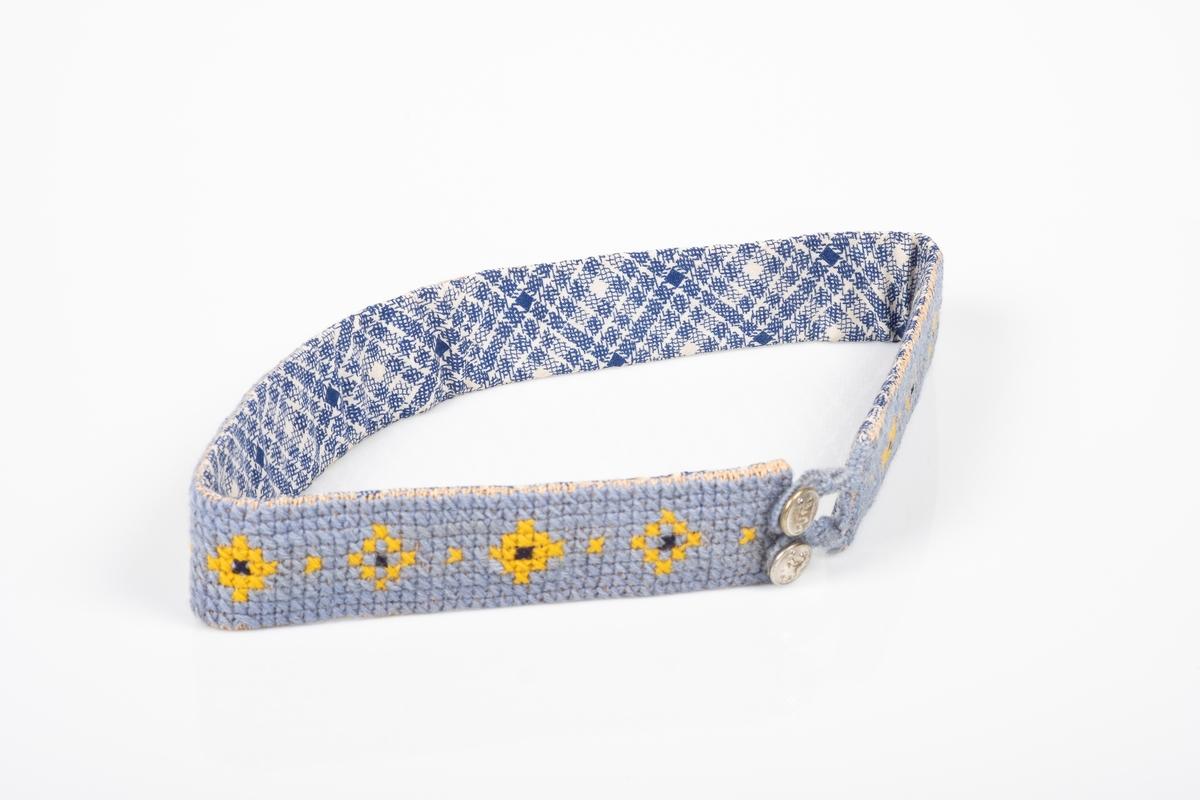 Brodert midjebelte som festes med to knapper. Beltet er brodert lyst blått med gult og svart mønster. Knappene har motiver av Den norske løven. Innsiden av beltet består av tekstil med blått rutete mønster.