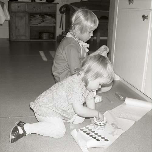 Två barn målar på papper utlagda på golvet, Glössbo 1972.