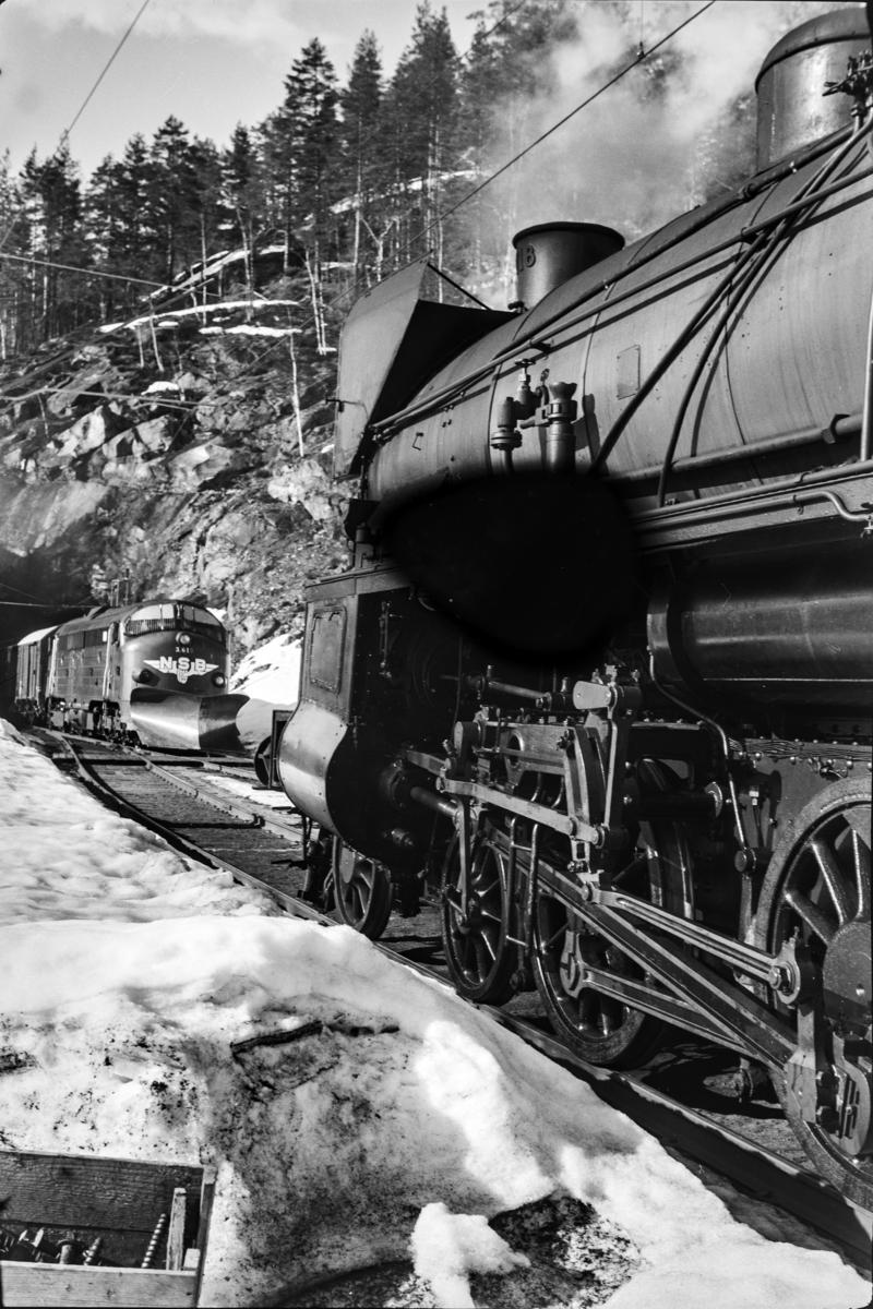 Kryssing mellom godstog til Bergen og ekstra persontog til Oslo Ø, tog 7624, på Ørgenvika stasjon. Godstoget trekkes av damplokomotiv type 31b nr. 418, persontoget av diesellokomotiv type Di 3 nr. 619.