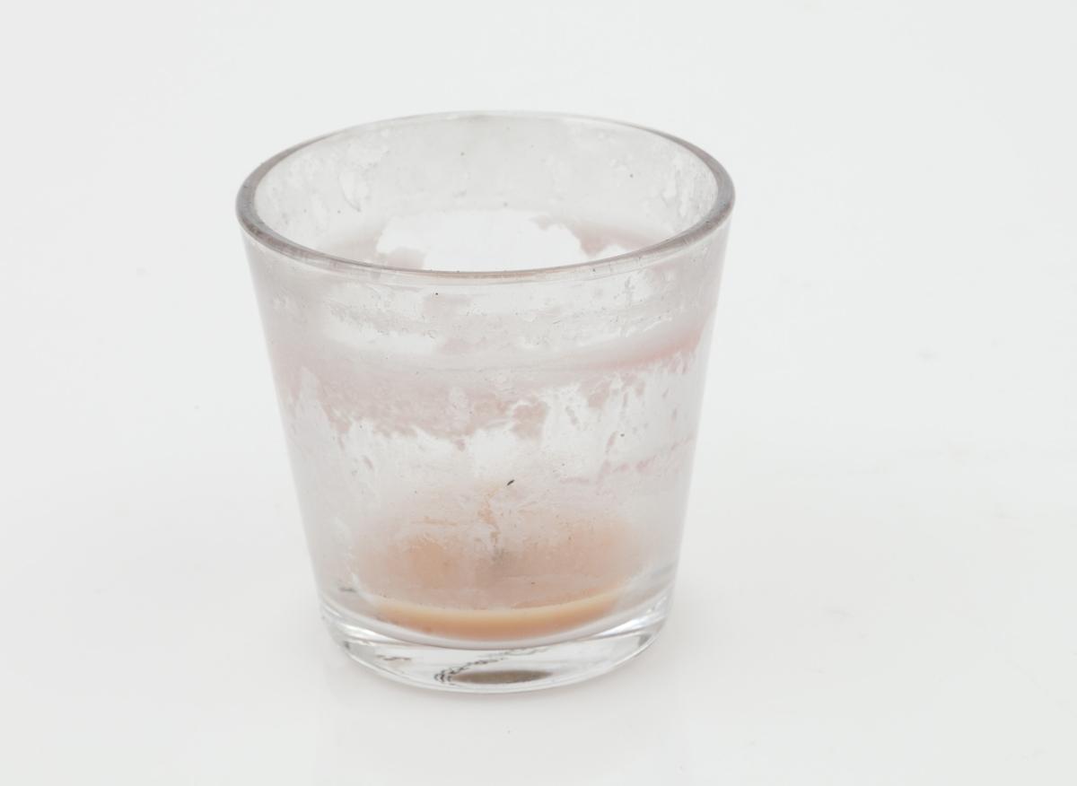 Telysholder innsamlet etter terrorhandlingen 22. juli 2011 fra minnesmarkeringene i Lillestrøm.   Dette er en liten telysholder i klart glass som har rester av stearin på innsiden av glasset. Fargen på stearinen er rosa. Den halve centimeteren med stearin i bunnen av lykten er oransje. Små sotpartikler forurenser restene av stearinen. Lyktens form er forøvrig videre øverst enn nederst. Under bunnen er det trykket på et nummer (produksjonsnr?) i sort.