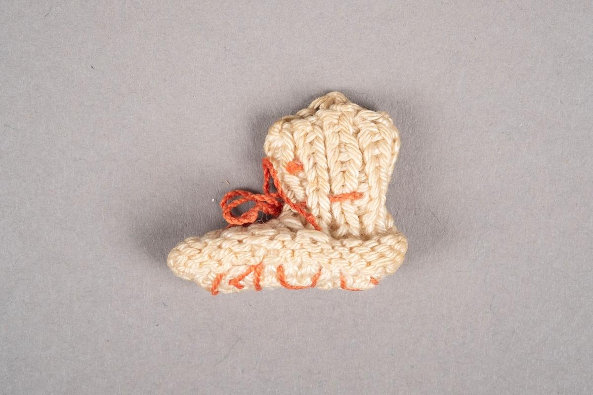 """Strikket miniatyrsokk. Sokken er strikket med hvitt garn. Den har rosa snøring. Det er brodert """"1944"""" på undersiden."""