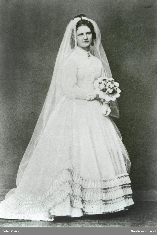 Bröllopsfoto Kristinehamn. Porträtt i helfigur av bruden prostinnan Sophie Lindström (född Lagergren) iklädd brudklänning med snäv ärm och volanger nedtill.