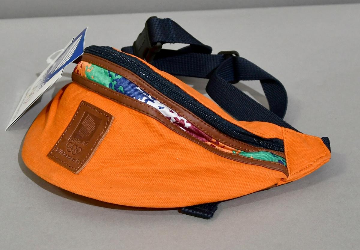Oransje rompetaske med glidelås og skinnkanter. Under glidelåsen en stripe med krystallmønster i grønt, blått, rosa, hvitt og oransje. Skinnmerke med emblemet for Lillehammer '94. Ekstra lomme med glidelås på innsiden.