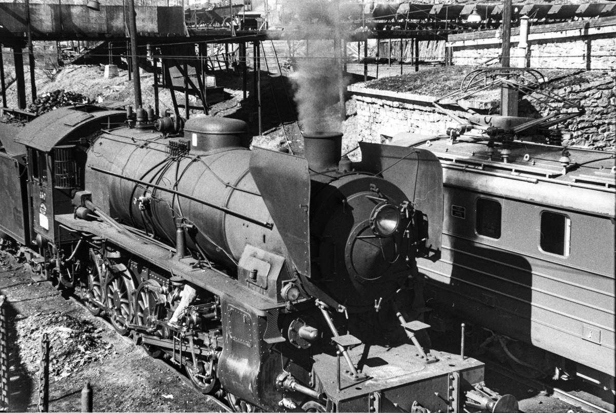 Damplokomotiv type 31b nr. 430 ved lokomotivstallen på Voss stasjon. I bakgrunnen trallebane med vagger for transport av kull til lokomotivene.