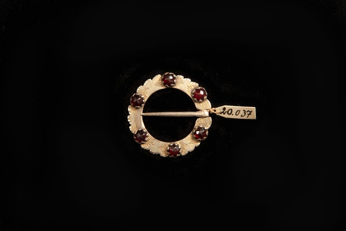 En rund ringsölja av silver med enkel graverad stråldekor runt sex små infattade stenar av rött glas. Uddig kant. Stämplad på baksidan.