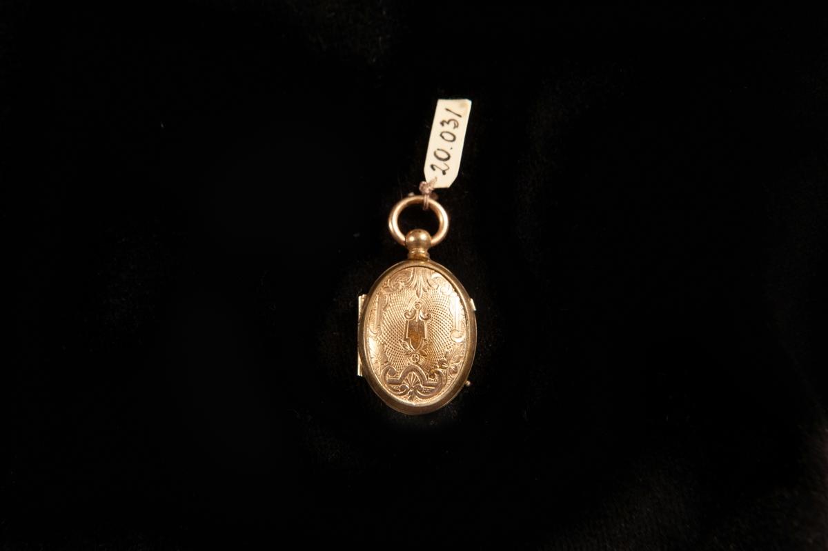 En oval medaljong i förgylld metall. Graverat mönster fram- och baktill i form av slingor m.m. i blandstil (nyrokoko/nyrenässans). Avsedd för två foton. Innanför ett av glasen finns en blond hårlock.  Ostämplad.