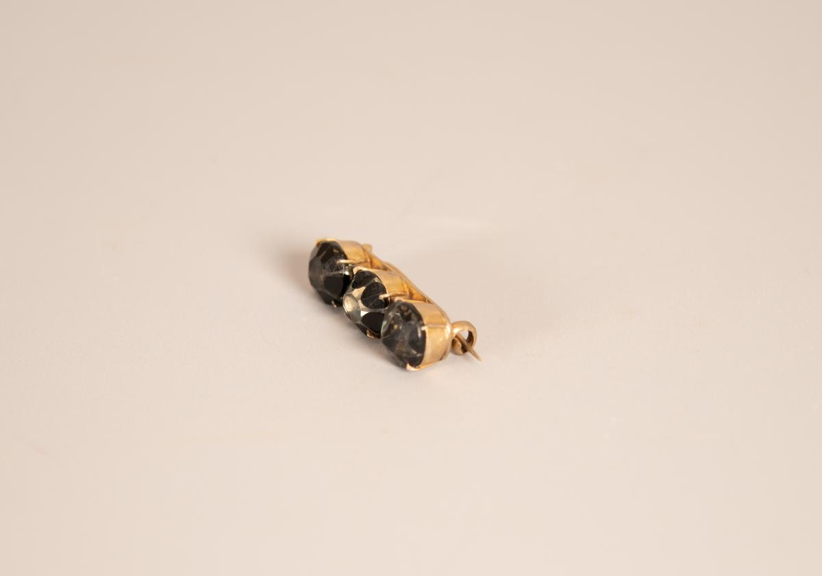 Langstrakt, plate med tre store stener i dyp innfatning. Stenene fasettslipt, den ene har en skarp spiss de to andre stenene er flate på toppen. Sortlakkerte tunger langs sidene, malt i ulike lengder så steinene får hvert sitt uttrykk. Hengslet  festenål.