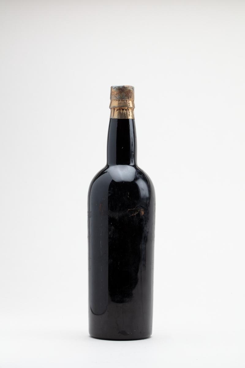 Madeiraflaske med innhold. Stensilerad trykket etikett med hvite bokstaver.