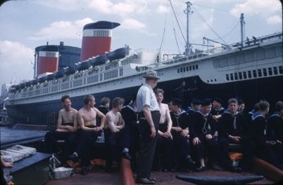 Kadetter fra skoleskipet STATSRAAD LEHMKUHL i baugen på en passasjerbåt på Hudson River. I bakgrunnen ligger passasjerskipet SS UNITED STATES fra United States Line som gikk sin jomfrutur fra New York til Europa 02. juli 1952.