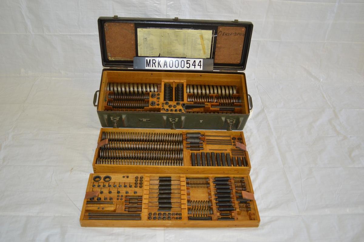 Plåtlåda med innanmäte av ek med olika lager av reservdelar och verktyg. Lådorna består av 2 - 4 lager.