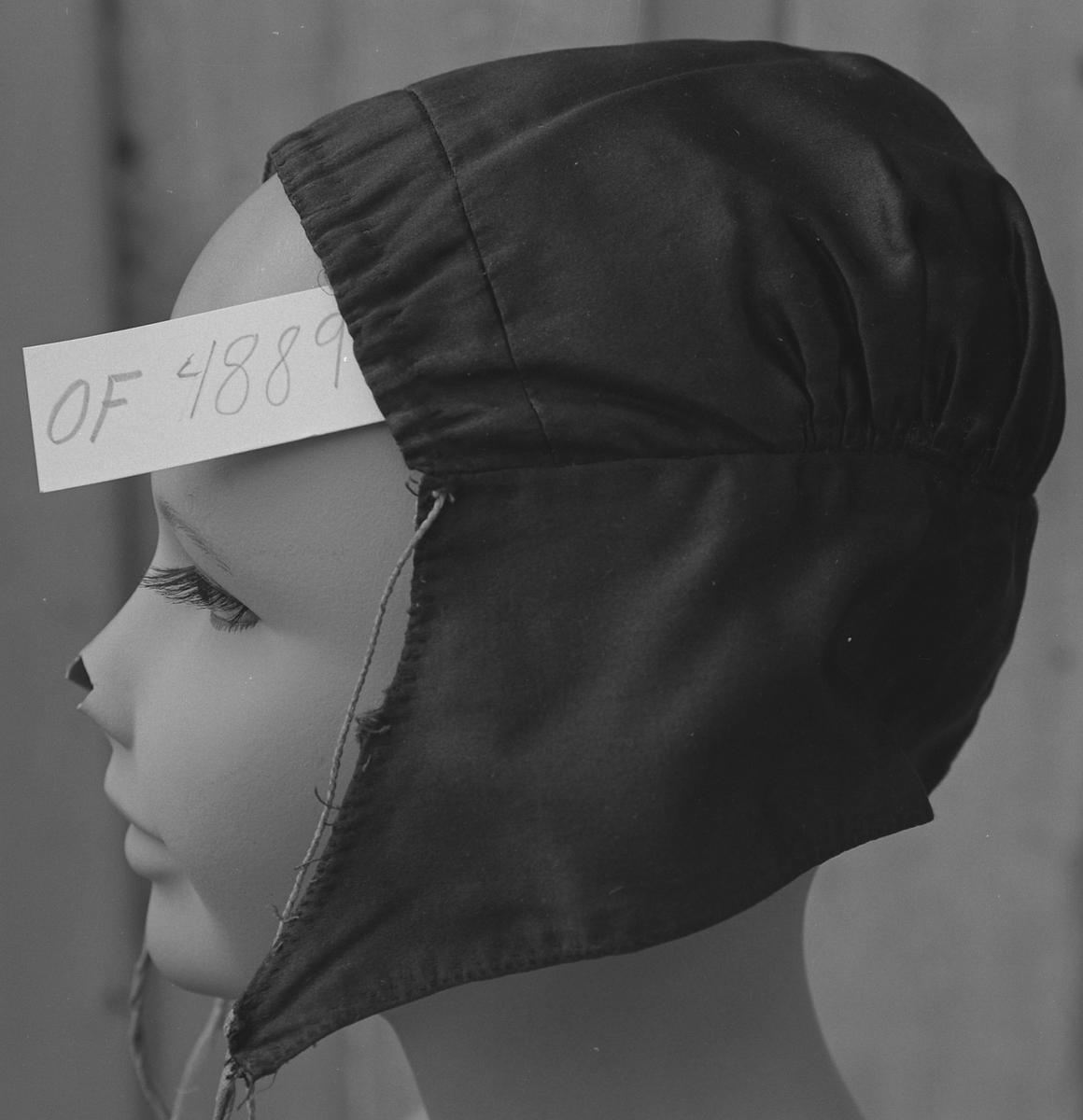 Rynkelue i svart silke, uten blonde, grovt fôr i bomull (ViVi, EIE sier lin), hakebånd og rynkesnor i bomull (ViVi, EIE sier lin).