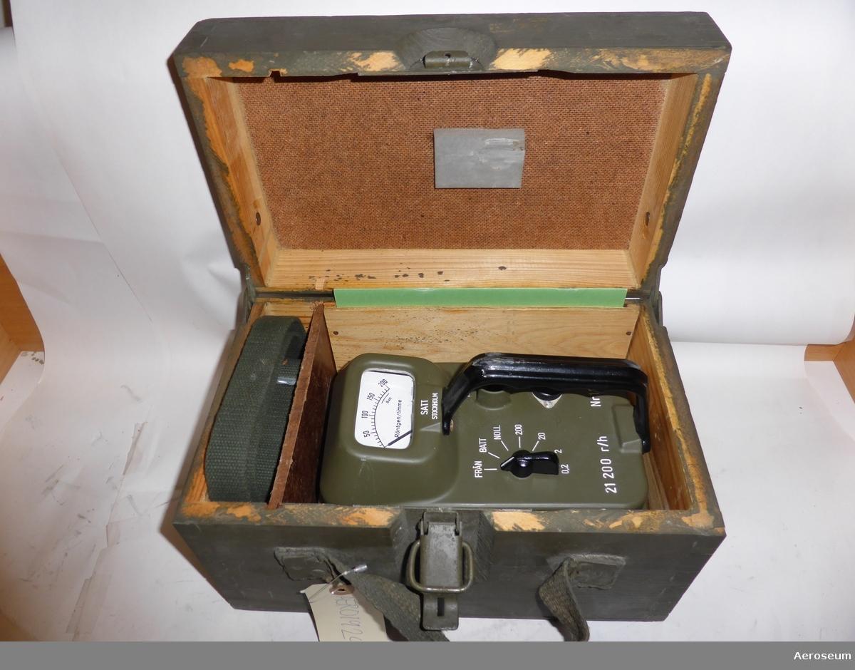 Intensimeter 21 placerad i grön trälåda tillsammans med en grön bärrem, en instruktionsbok, plastpåsar, och en plastpåse med rödvitmönstrade pappersremsor i hård kartong.