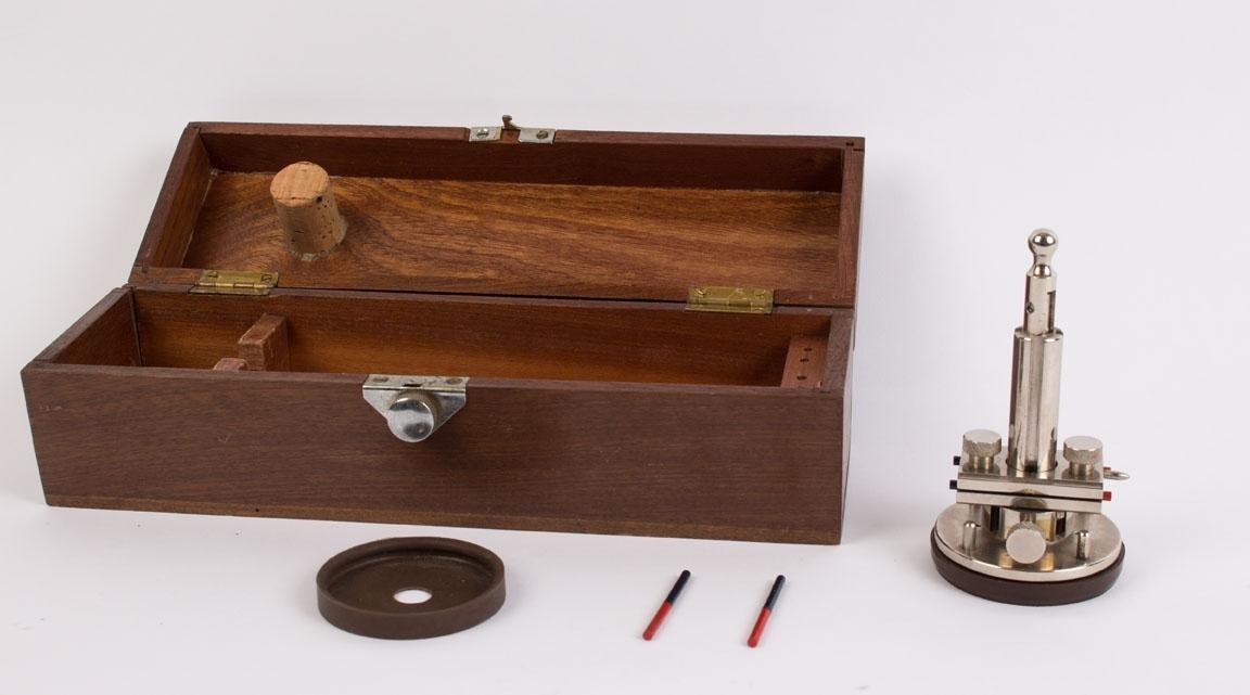 Deflektor med to magnetstaver, linjal og ekstra gummiring for montering på sokkel. Ligger i liten trekasse med lokk.