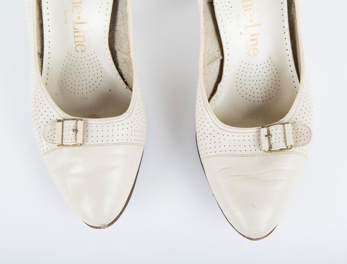 """Hvite sko med spenne.  """"Fine Line sko fra ca. 1964, kjøpt hos skomaker Pedersen i Drøbak. Husker at de ble brukt da en av mine brødre ble døpt i gamle Frogn kirke i 1961."""" Tidligere eier"""