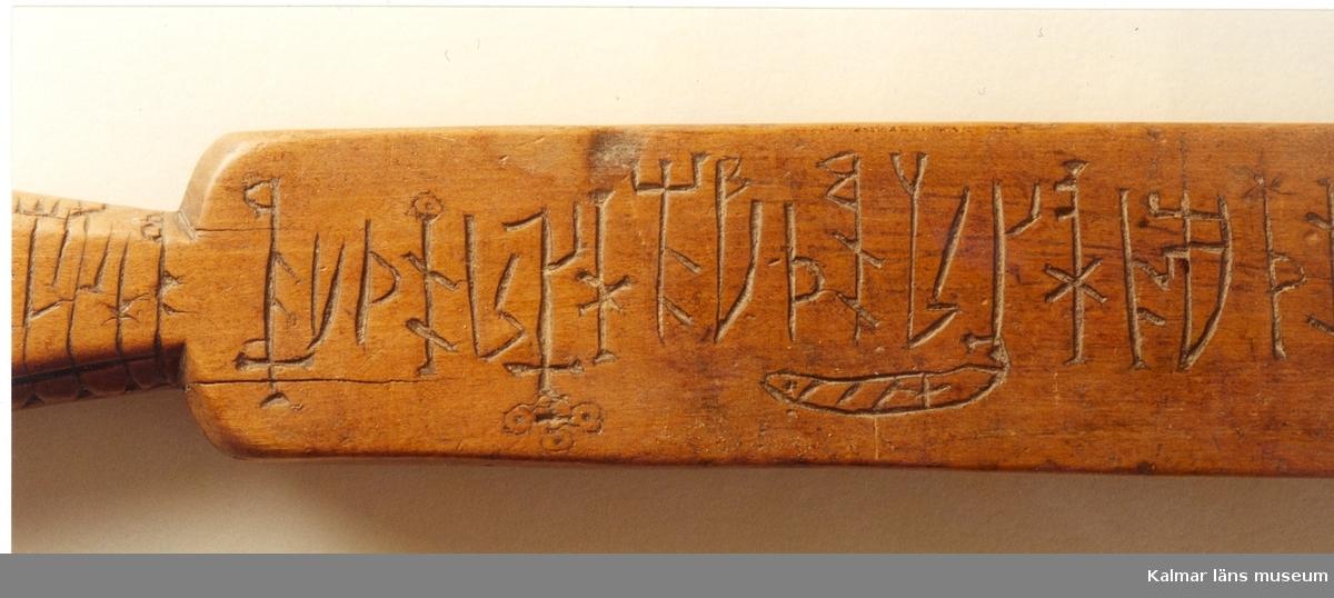 KLM 7769. Runstav. Trä, platt fyrsidig med svärdfästeliknande handtag. Runor på båda sidor. På handtaget flera initialer: AD E, PS, AE.