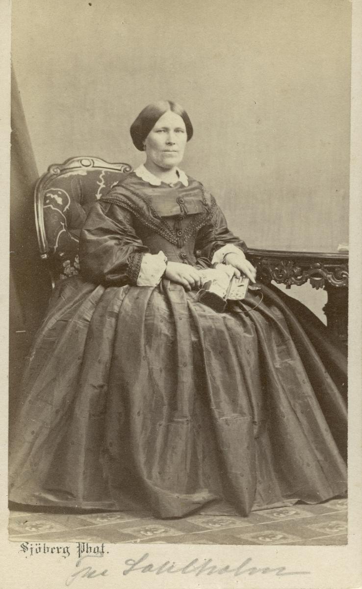 Fru Sahlholm med virkning och etui i händerna. g.m. Handlare C. J. Sahlholm.