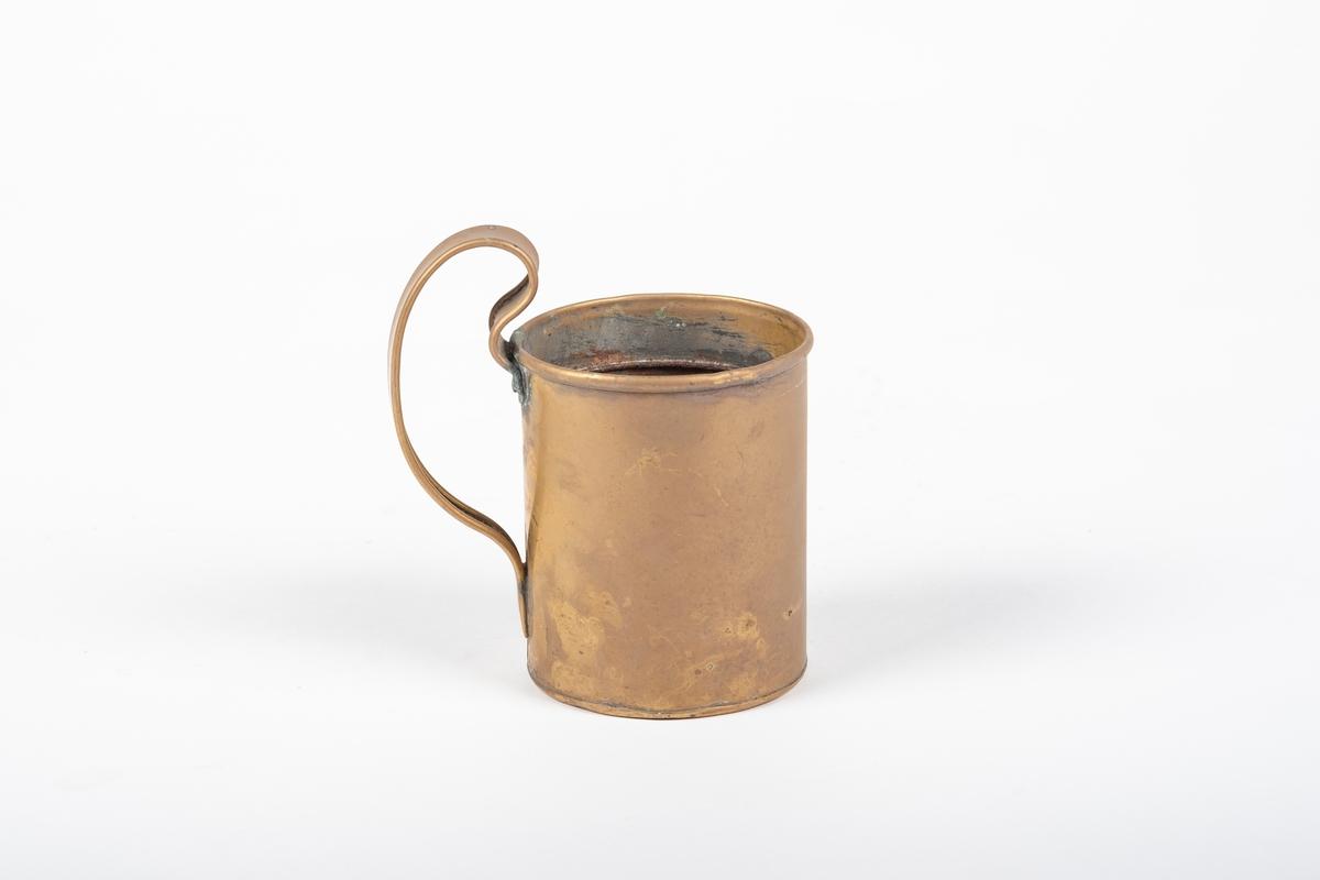Kopp med rund grunnflate og rette vegger, og med hank som krummer seg litt over koppen.