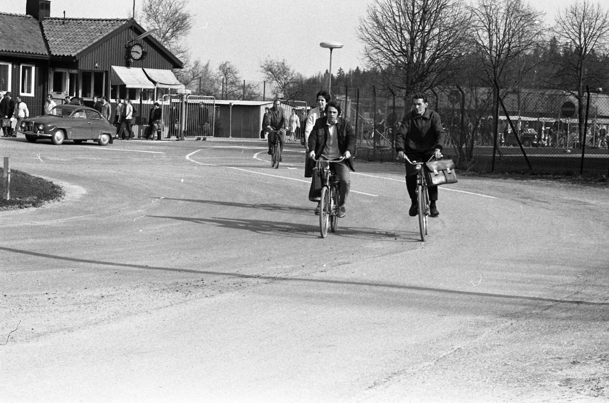 """Arbetsdagen är slut, på CVA, Centrala Verkstaden Arboga. Folk passerar grindarna på väg hem. Några män kommer på cykel andra är på väg till bilparkeringen eller busshållplatsen. En SAAB är parkerad utanför """"vakten"""" (huset till vänster, där vakten sitter)."""