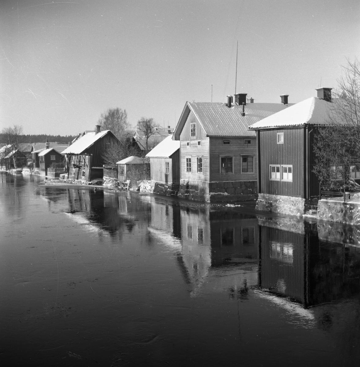 """Vintermotiv. Ågårdag på Västerlånggatan, Arbogaåns norra sida. Det är snö på taken. (""""Lutande huset"""" revs i april 1969)"""