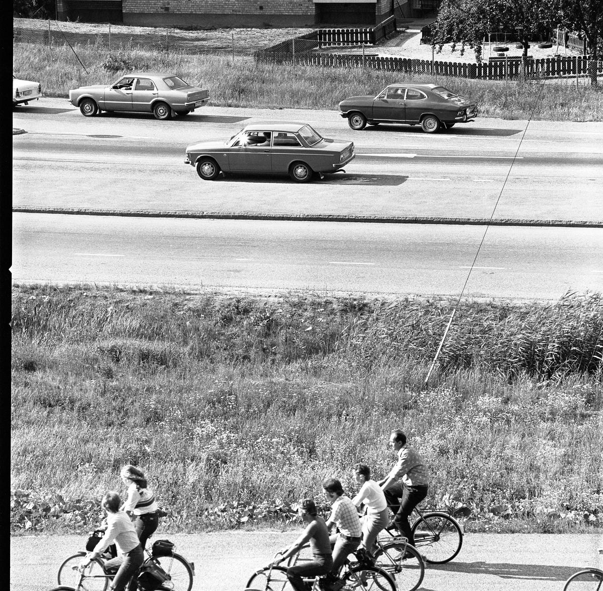 Cyklister och bilförare på Västermovägen, Brattberget. Daghemmet Biet ses i bakgrunden.