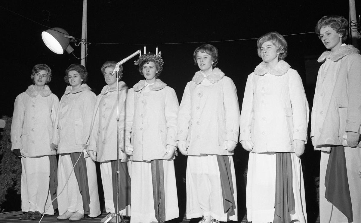 Lucia har krönts på Stora torget. Nu står de, uppställda, iklädda vinterjackor, linnen och röda band. Från vänster. Iréne Johansson, Margareta Norman, Christina Hedqvist, Britt-Marie Gustavsson (Lucia), Hjördis Holmqvist, Monika Norén och Gerd Eklöf.