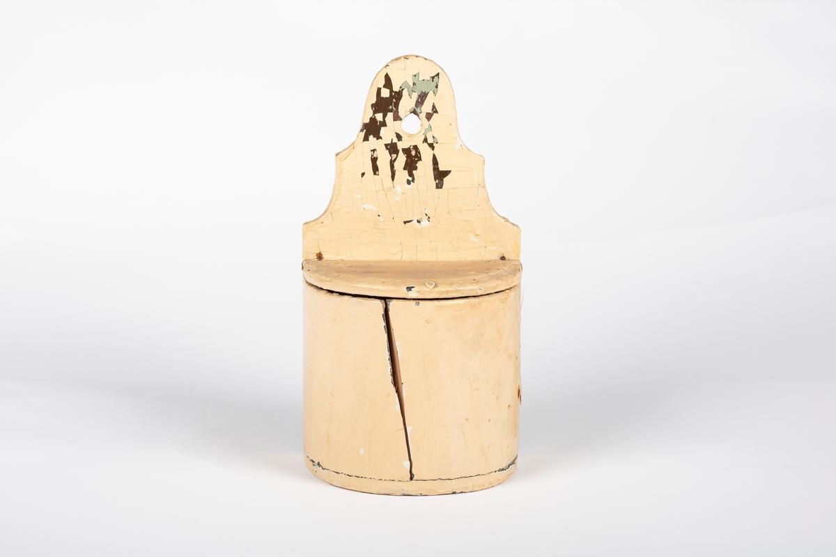 Beholderens grunnflate er en halvsirkel. Den bakre platen stikker høyere opp enn selve beholderen. Den øvre delen av bakplaten er skåret i en dekorativ form og har et hull øverst slik at den kan henge opp på veggen. Beholderen har et lokk i tre. Det ser ut som beholderen har vært malt flere ganger i andre farger.