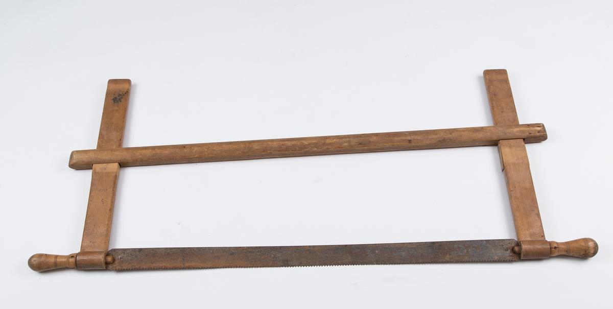 Grindsaga består av en bom med to armer som har øye i nederste.