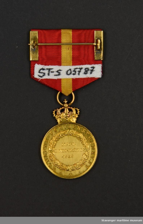 Kongens Fortjenstmedalje i gull. Medaljen er rund med kongekrone på toppen. Kong Haakons profil er preget på medaljens forside med tekst. På baksiden en krans med tekst i midten.