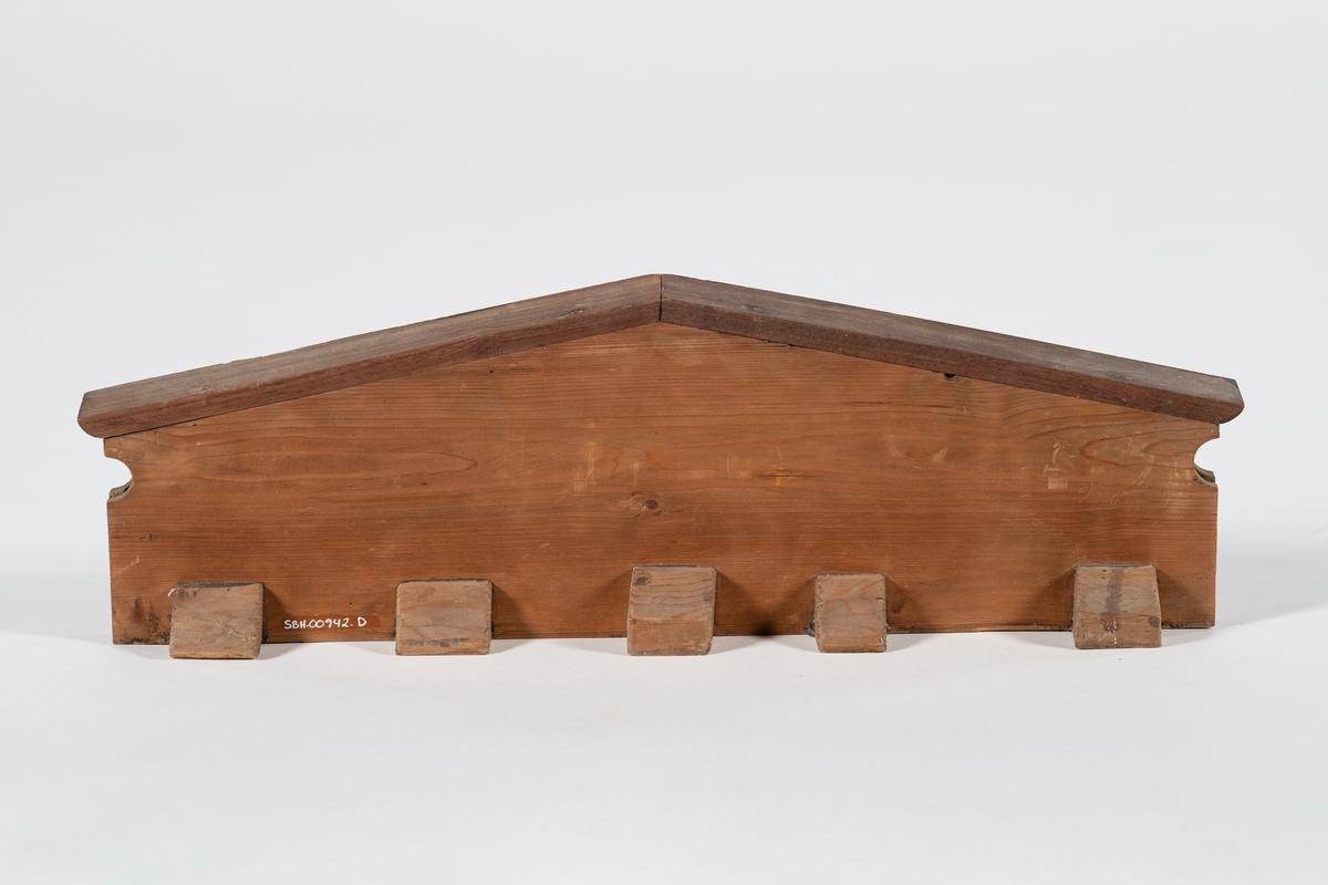 Kronlist til sengekrone med skrånet kant øverst. Kronlisten består av to planker limt sammen hvorav den ene er skåret ut. En halvsirkel skåret inn i hver kortside. På baksiden er det pålimt fem støtteklosser.