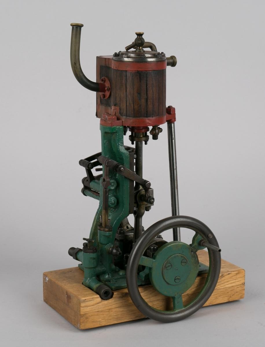 Dampmaskinmodell, 1- sylindret med oppstående kjele/dobbel plate av tre  og metall med dreiehjul på siden.  Montert på tresokkel.