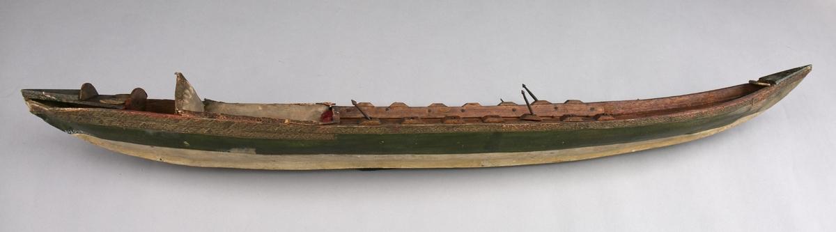 Modell av lystfartøy fra Østen. Større rogalei rikt dekorert. Akter er det en polstret sittegruppe trukket med silke samt dørken er belagt med skinn. Flere løse deler medfølger.