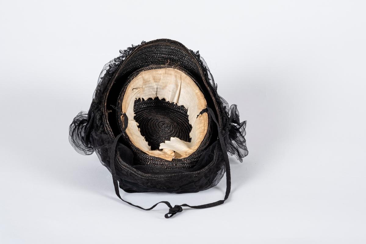 Brun, oval stråhatt drapert med to foldede fløyelsbånd og ett tyllbånd med rosetter i hver side. Ved den ene rosetten er det festet en onamentert pyntenål med dekorstener. Langs kanten er bremmen dekorert med perler og blonder, dette er delvis dekket av tyllbåndet. På undersiden er det svettebånd og hakesnor.