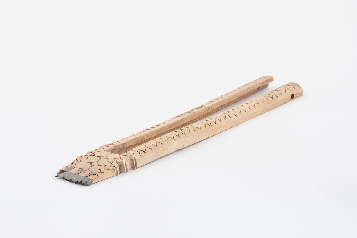 Del av vevspenne av tre, ytterdelen. Vevspenna har utskåret bølgeformet dekor, samt utskjæring i den ene enden. Det er et beslag av metall i den ene enden med pigger.